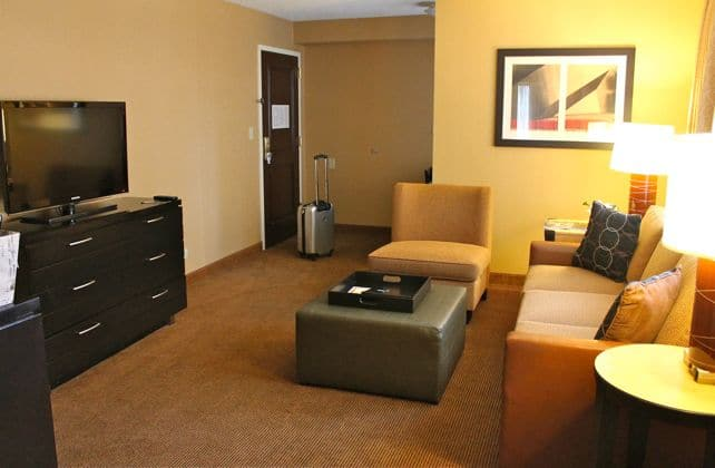 The living room area of the Embassy Suites Chicago Downtown has a pull-out couch, chair and a TV.