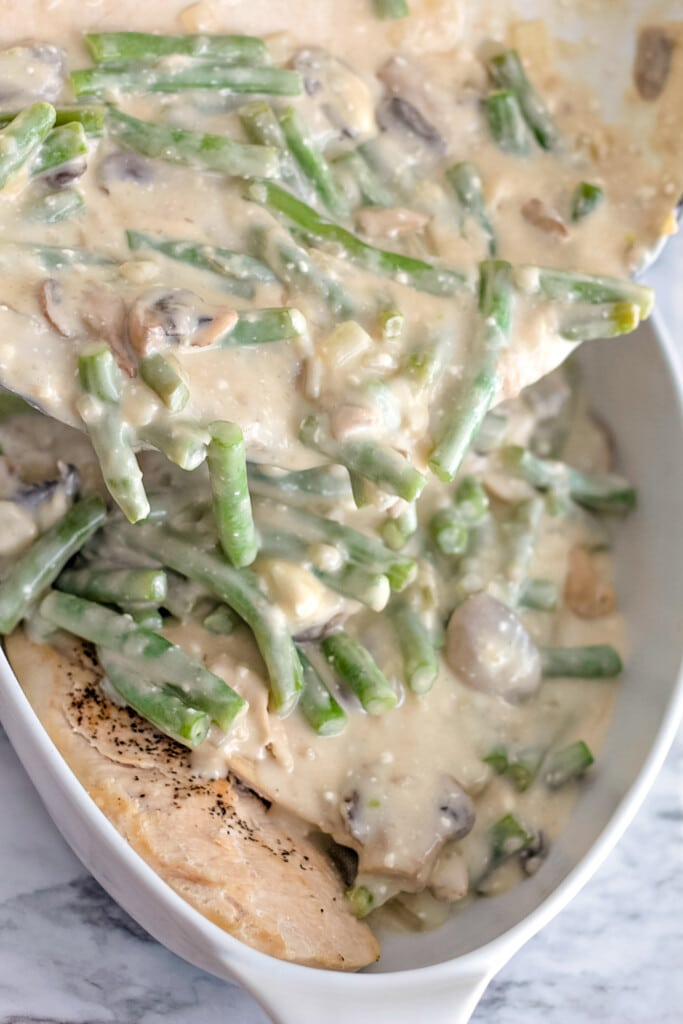baked chicken topped with green beans and mushrooms in a cream sauce