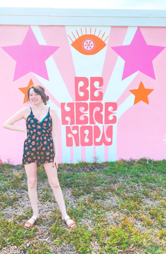 girl in front of be here now wall mural
