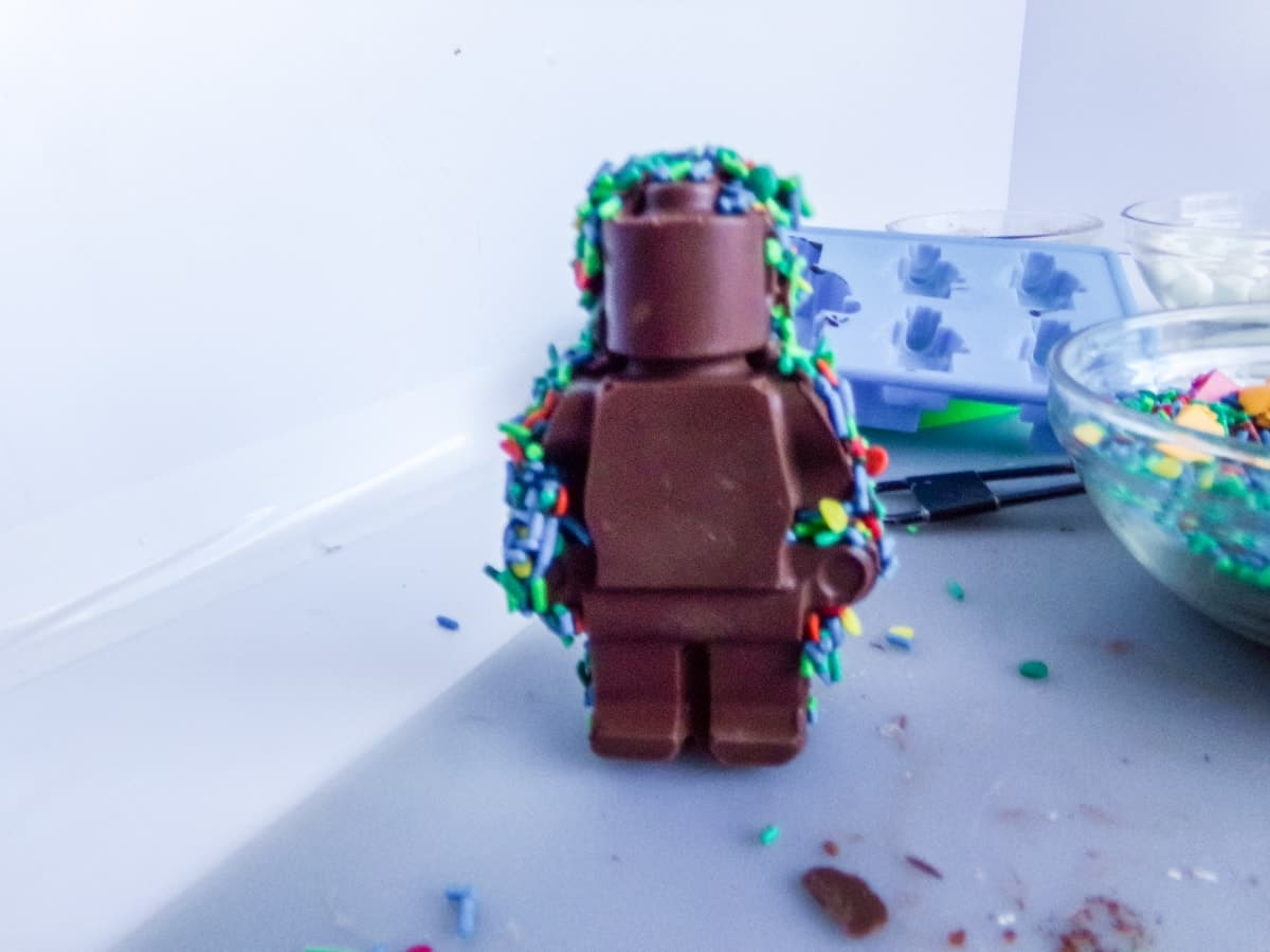 adding sprinkles to the edges of a Lego Man Hot Cocoa Bombs