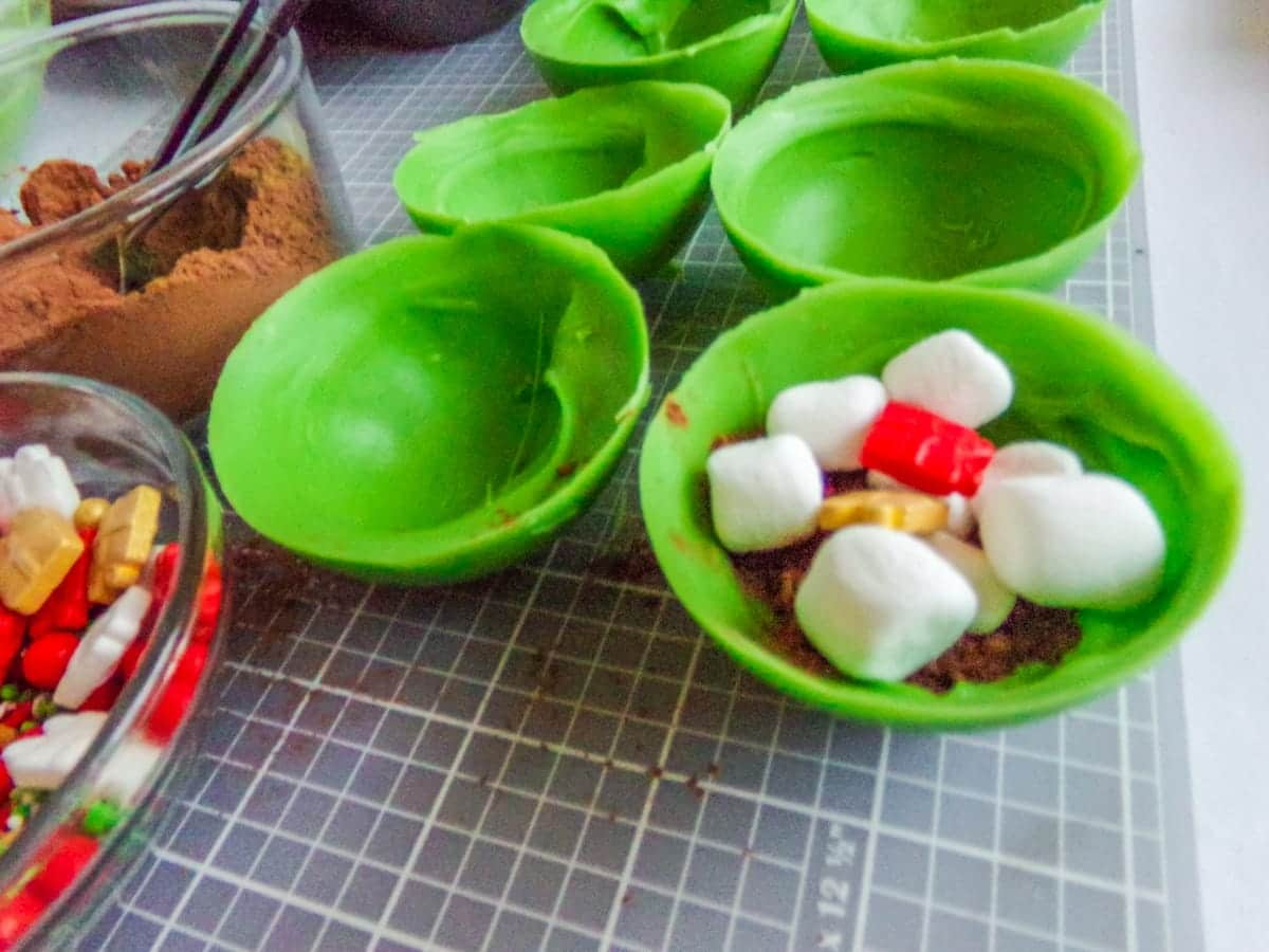 filling Christmas Hot cocoa bombs with marshmallows