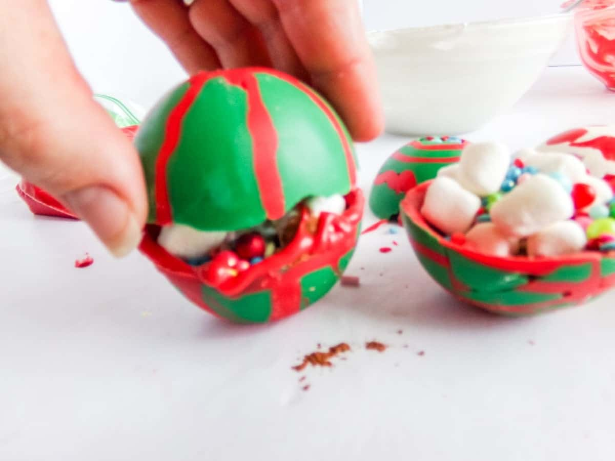 in-process step of closing up Christmas Ornament Hot cocoa bombs