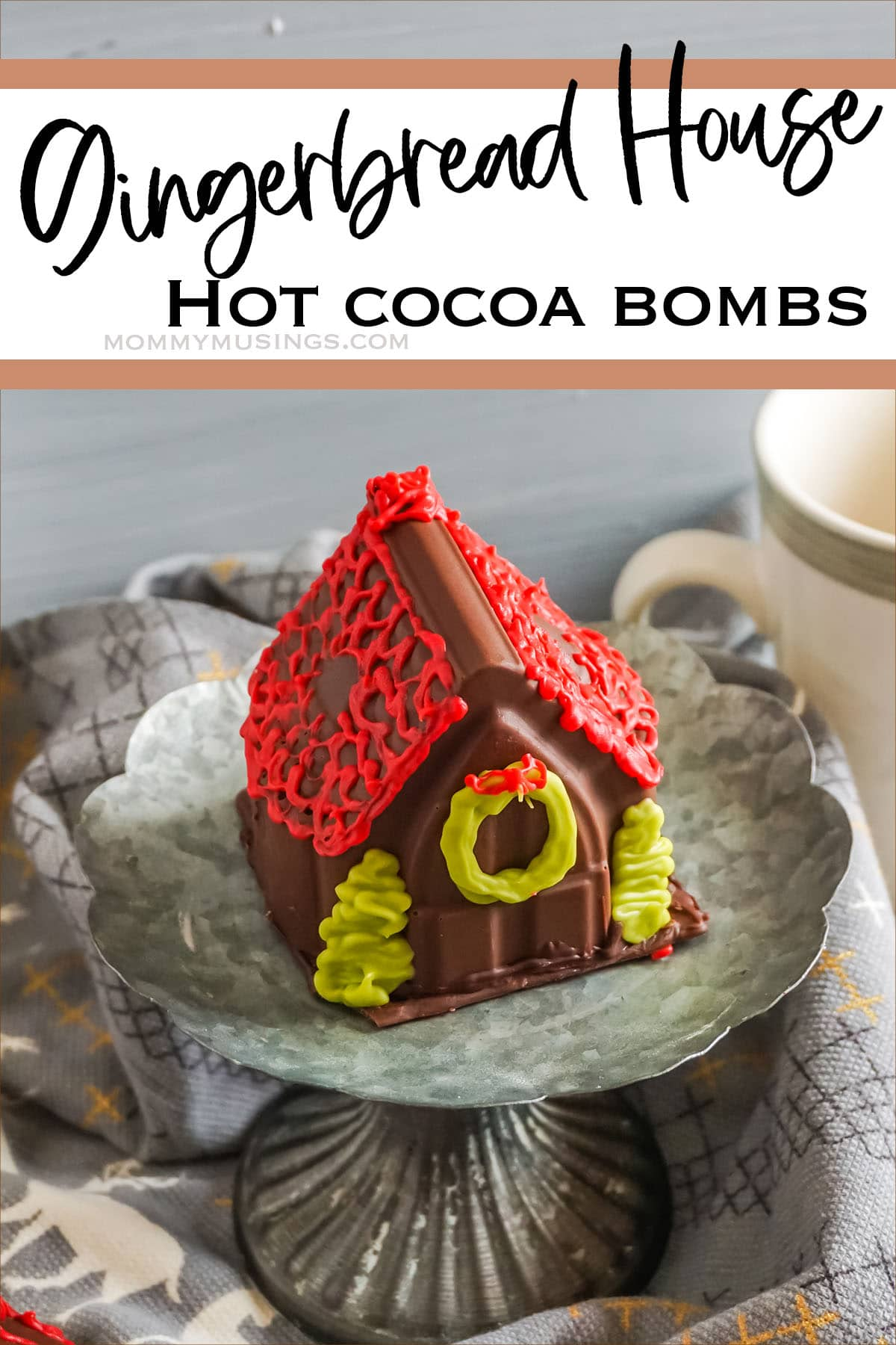 gingerbread house hot chocolate bomb on a cupcake stand with text which reads Gingerbread House Hot Cocoa Bombs