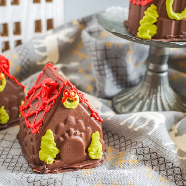Gingerbread House Hot Cocoa Bombs on a table with a mini house cutout