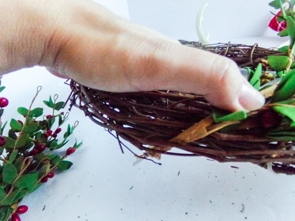 in-process step of attaching greenery to make aMickey Reindeer Wreath