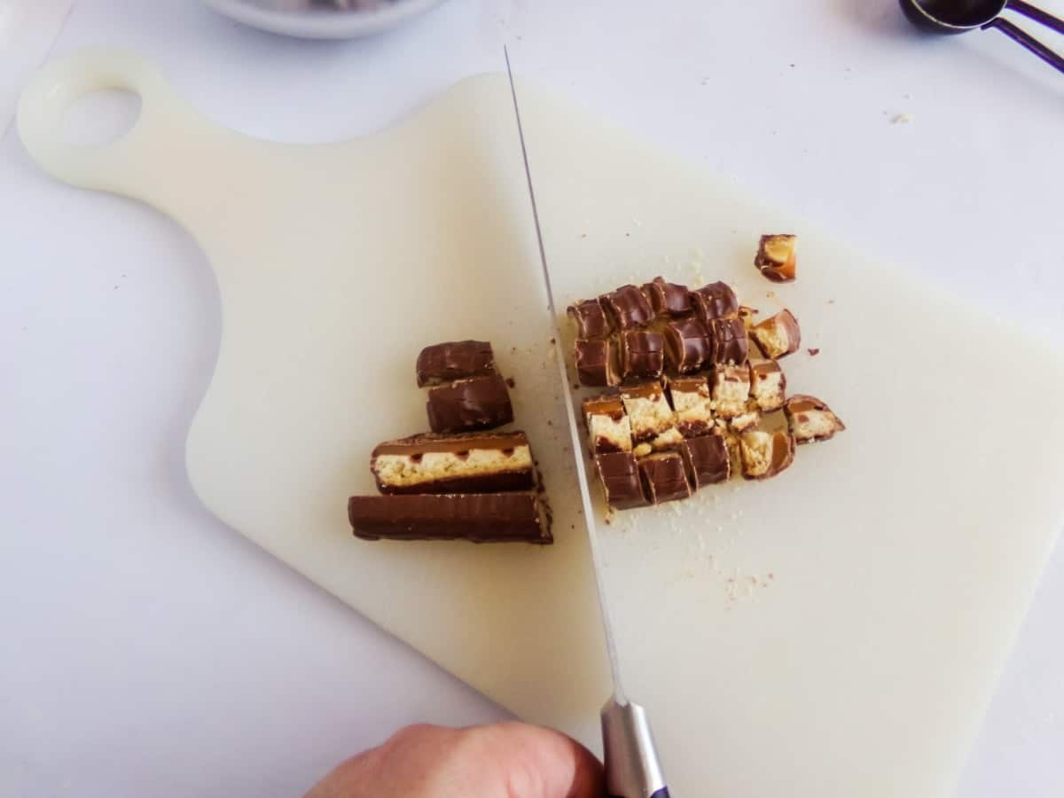 chopping candy bars to make twix hot cocoa bombs