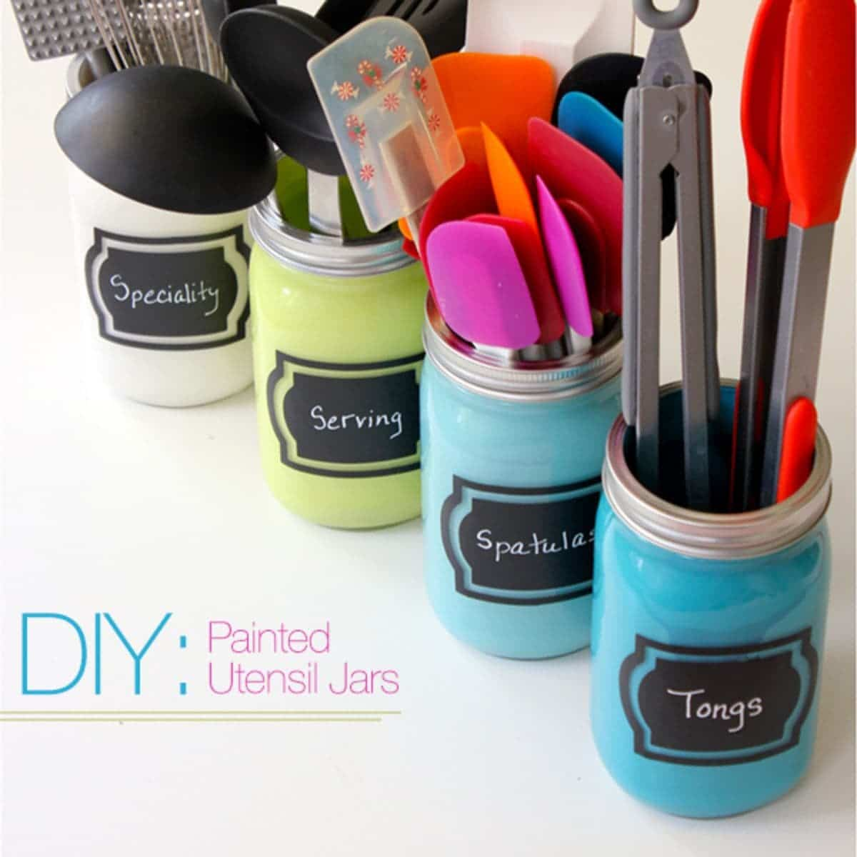 4 mason jars in a row, each colored in pastels: blues, turquoise, yellow and cream. They have black labels on the front with chalk writing. They each contain kitchen utensils