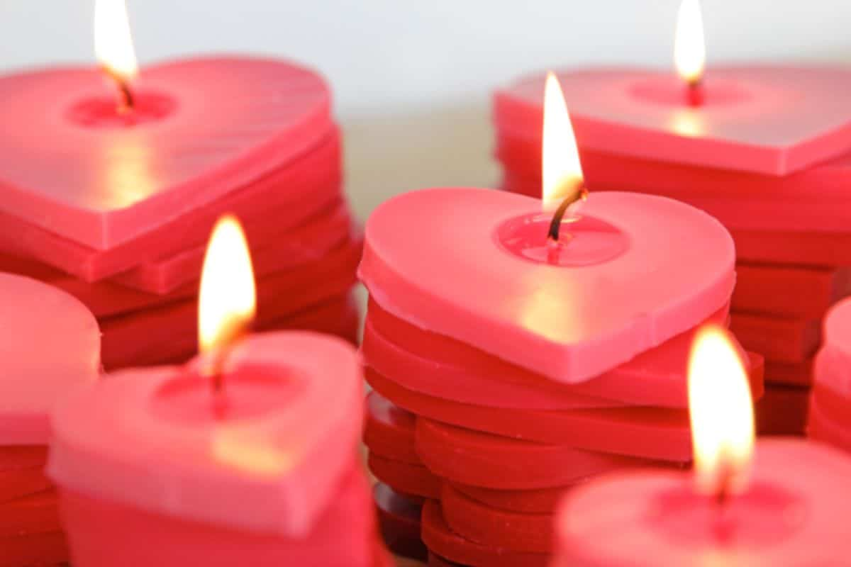 piles of red wax hearts are stacked and lit with a flame
