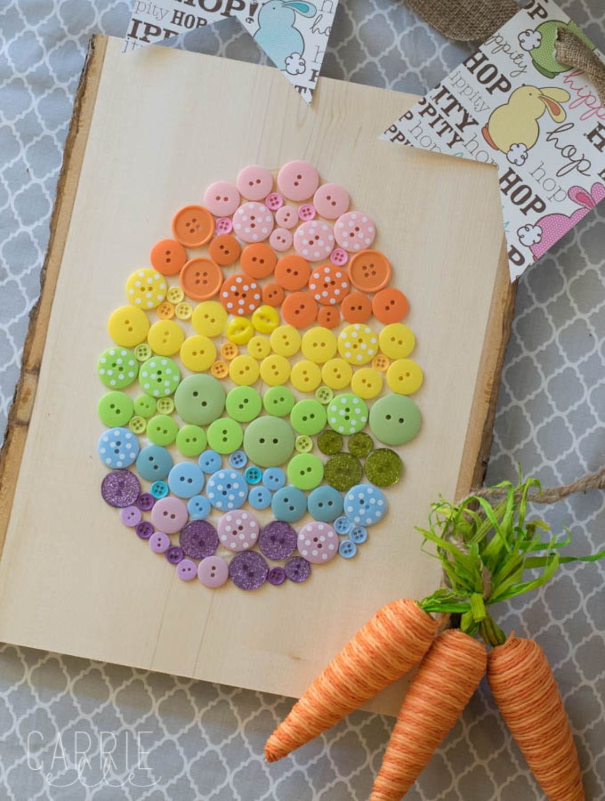 A striped egg made of different colored buttons is stuck to a canvas sheet. Next to it sits 3 material carrots