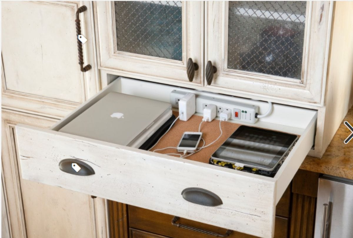 A cream dresser has a drawer open. Inside the drawer is a laptop, phone and ipad. At the back of a drawer is a power bank which the devices are plugged into