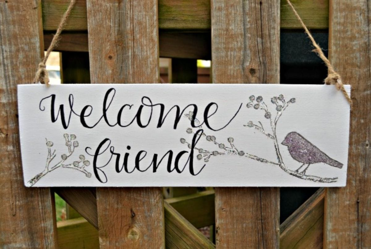 """A painted sign is hanging from a crate. Words say """"Welcome friend"""" and there is a drawing of a bird to the right"""