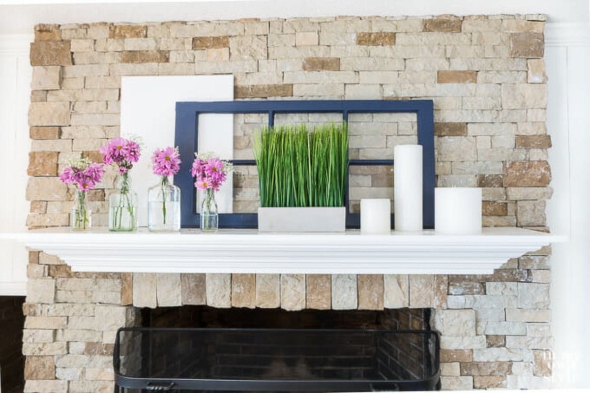 A mantelpiece is on a brick wall. There are 2 empty picture frames, some flowers in vases and a white ceramic pot filled with green stems