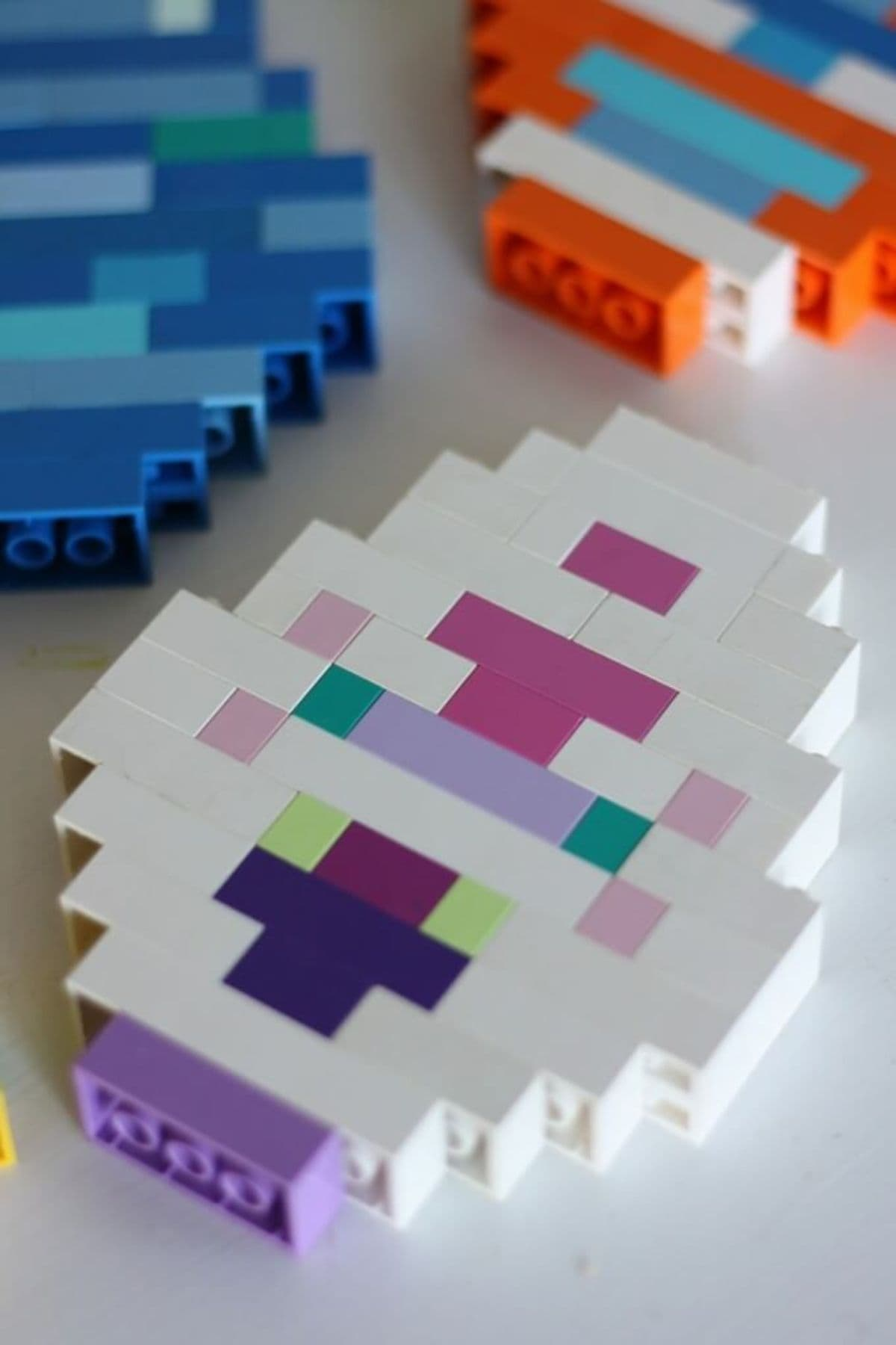 A blue egg, purple and white egg, and orange white and blue egg all made of lego are laying down on the surface