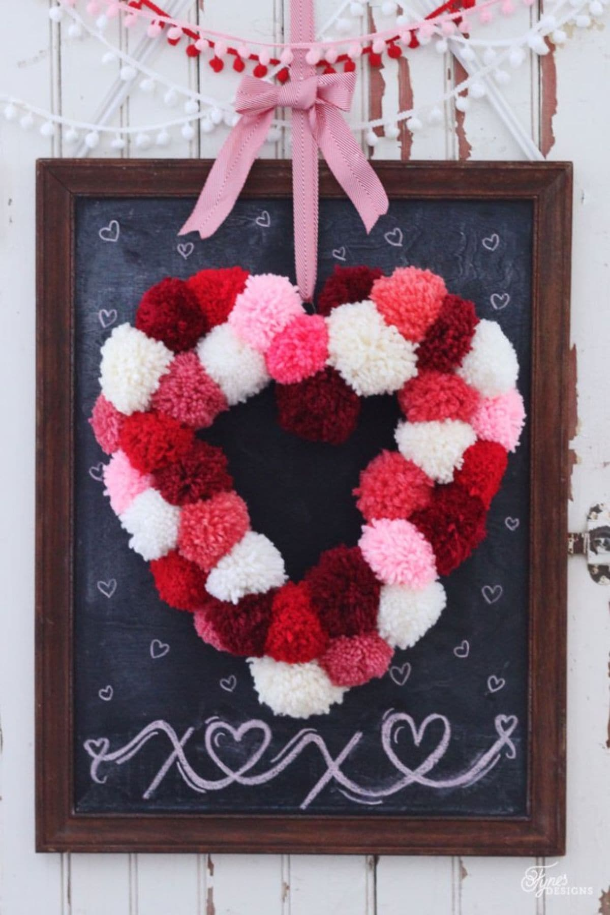 Hanging from a framed blackboard by a pink ribbon, is a heart made out of pom poms in reds, whites and pinks.