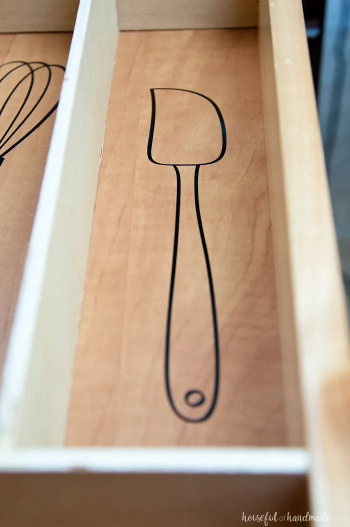 A close up of a section of a drawer with wooden dividers. There is a black pen drawing of a spatula on the bottom of the drawer