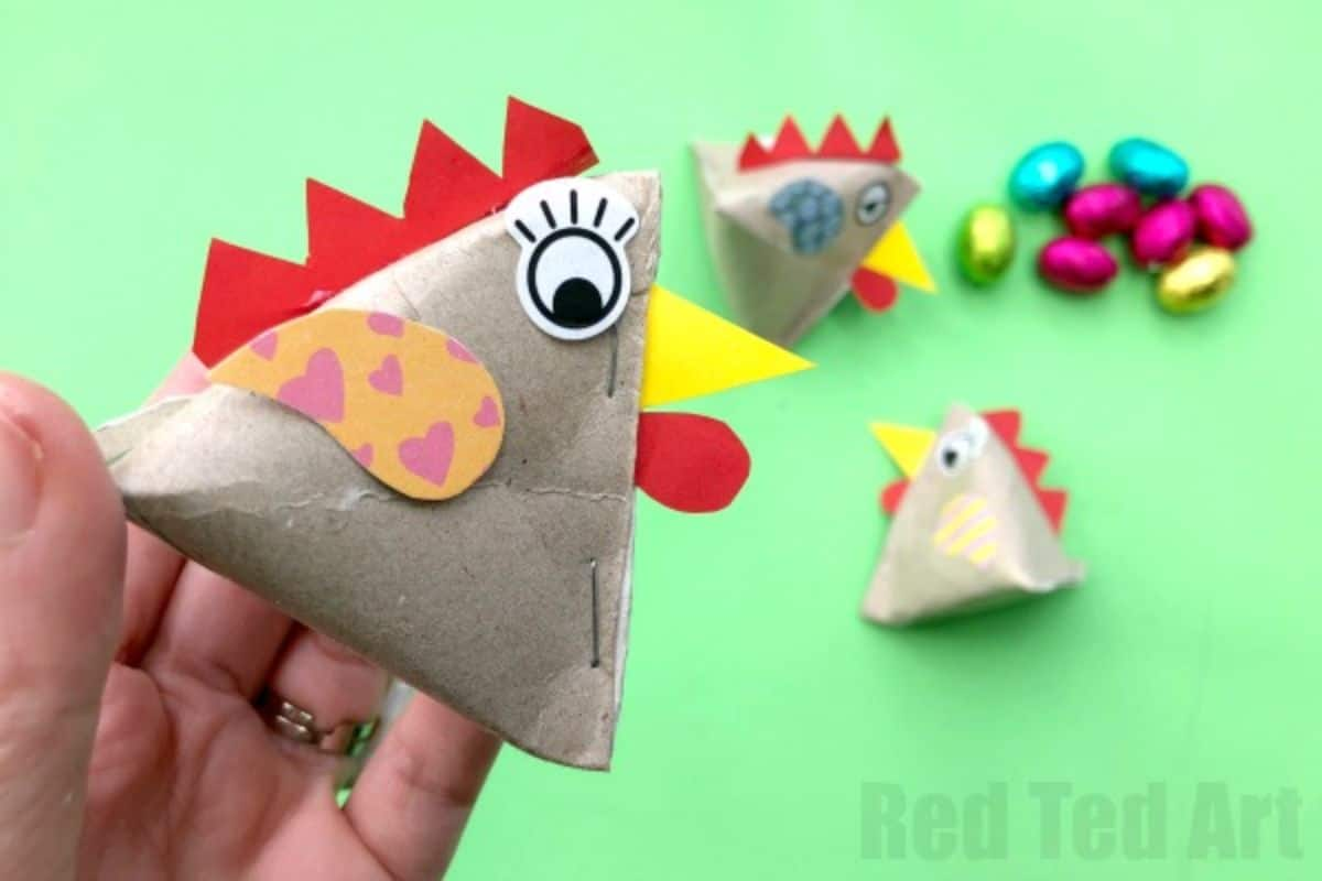 a hand holds a pyramid of paper decorated to look like a chicken, with 3 more in the background