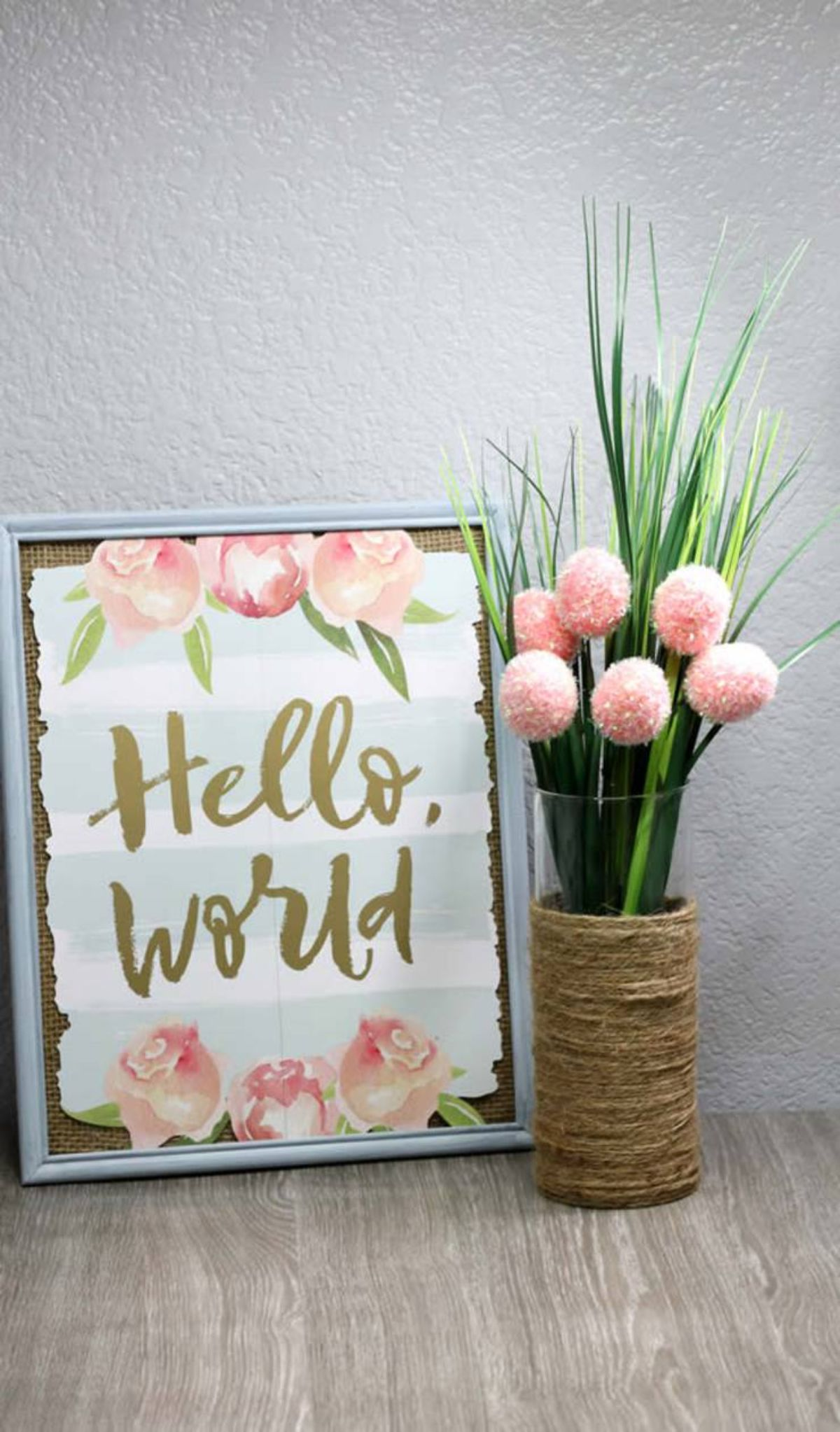 """Next to a painted sign saying """"hello world!"""" is a thin glass vase filled with tulips. Twine is wrapped around the bottom half of the vase"""