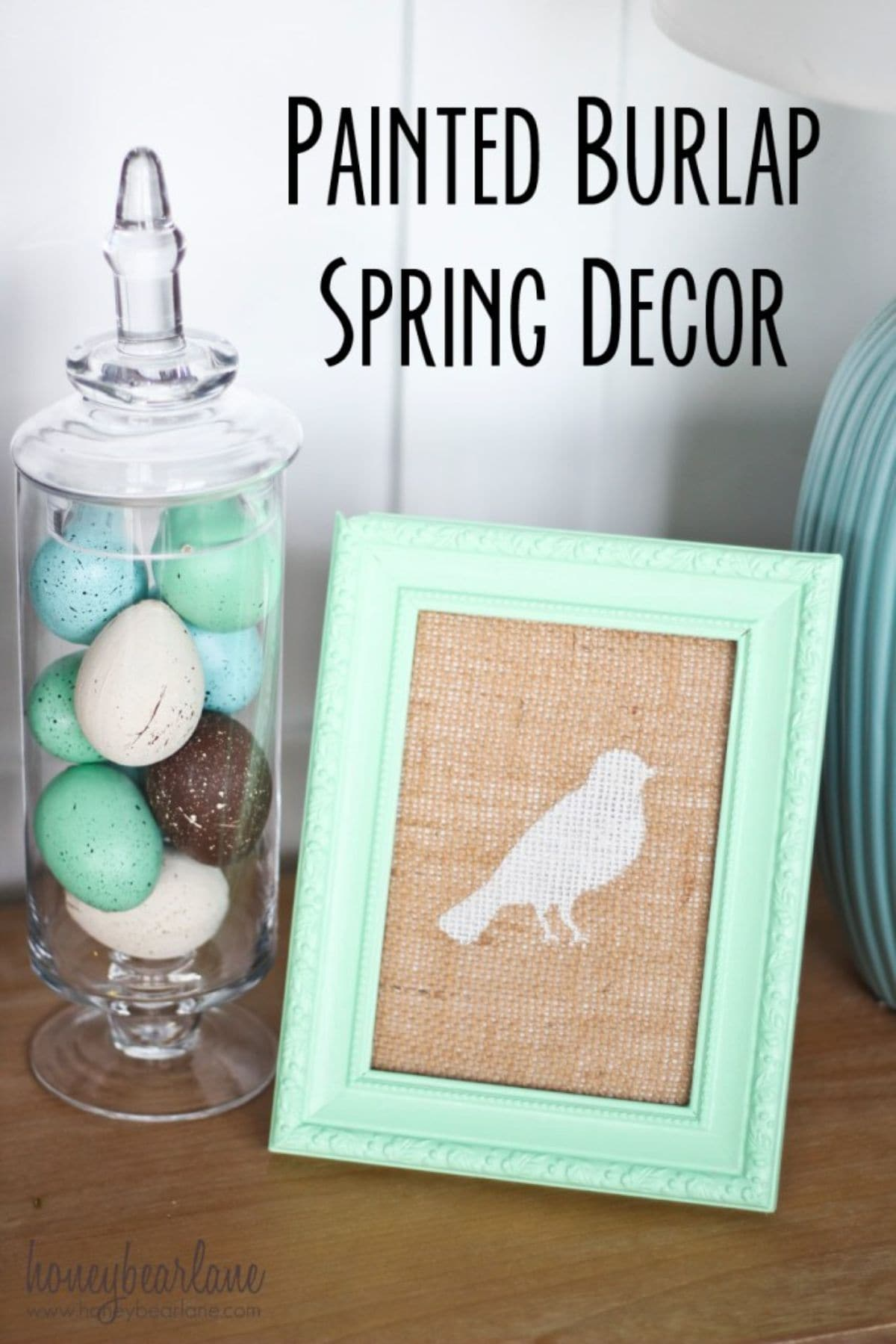 On the left of the picture is a glass jar full of colored eggs. On the right is a burlap sheet with a green painting of a bird on it, it is framed in green