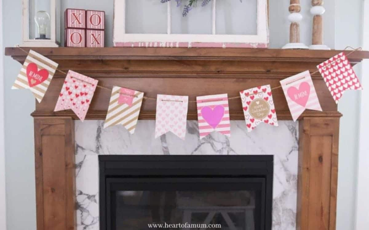 A wooden mantelpiece is pictured. Hanging from it is a garland made of paper flag shapes in different designs