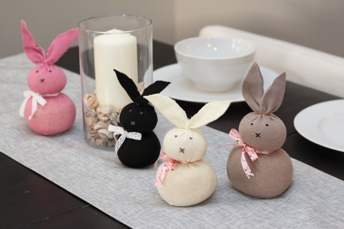 4 bunnies, pink, black, cream and grey sit on a table runner in front of a candle in a glass lantern