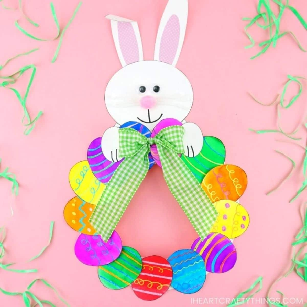On a pink background a curcle made of colored paper eggs sits underneath a bunny's head