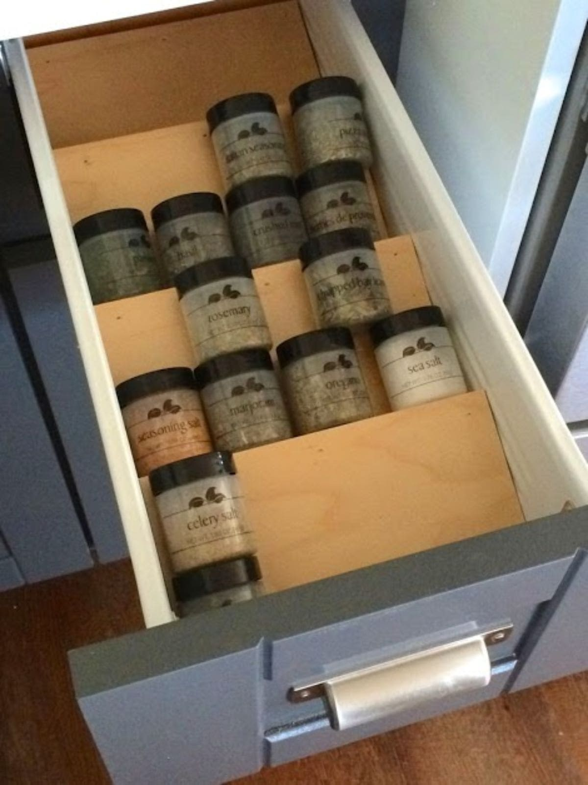 Inside a kitchen drawer are some slanted pieces of wood. On each shelf are small galss spice pots