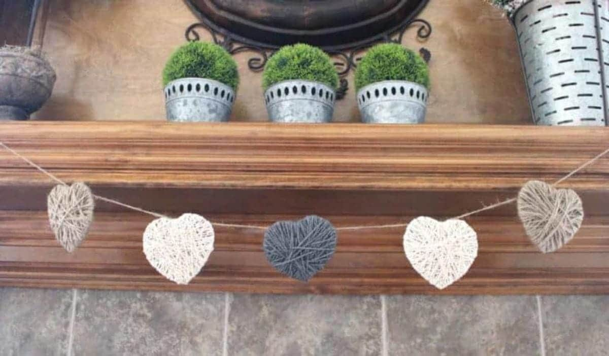 A wooden mantelpiece is decorated with 3 metal plant pots filled with gree, bushy plants. Hanging from the mantel is a garland of yarn hearts in greys and whites