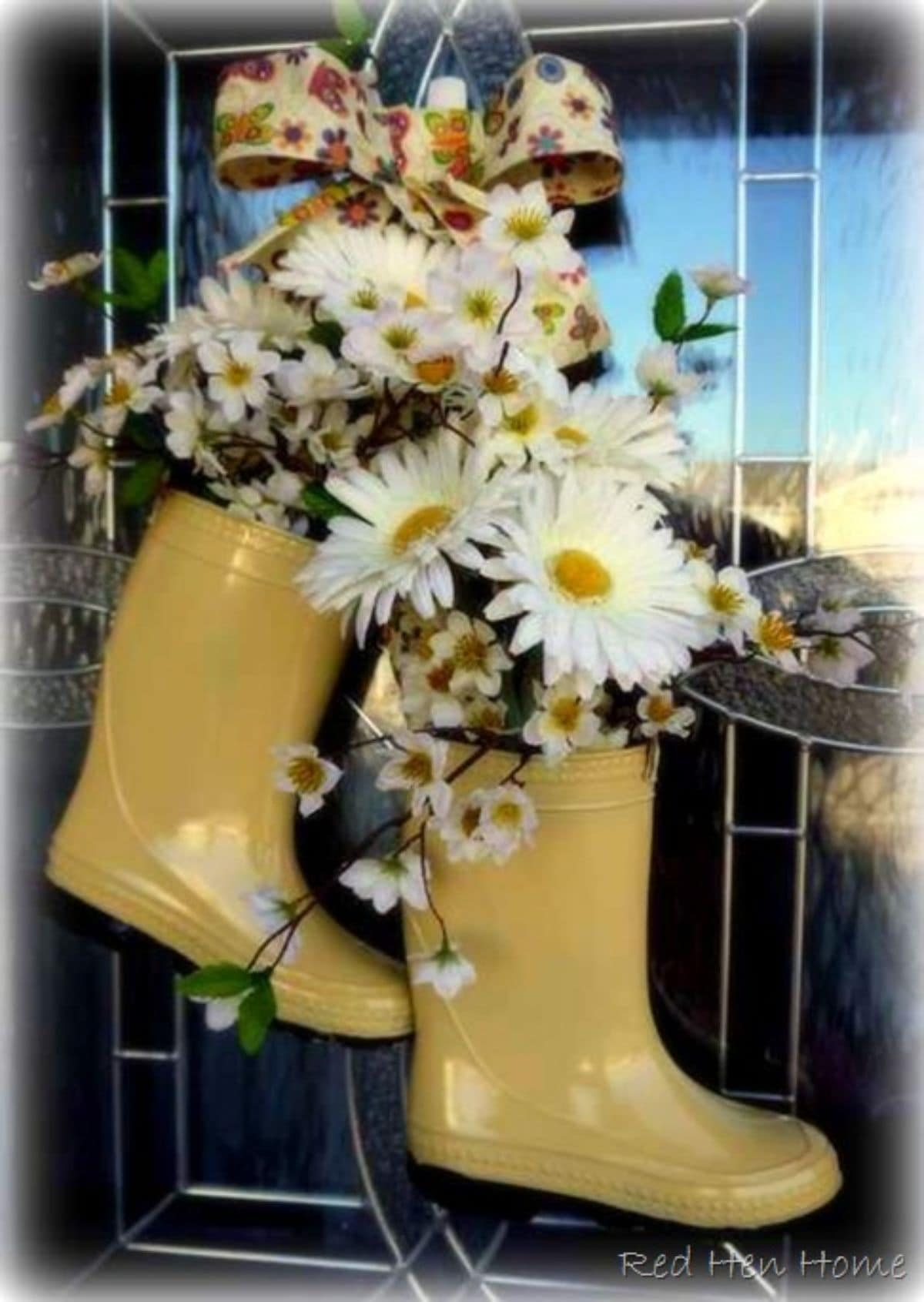Hanging from a front door are two yellow wellies filled with white and yellow flowers