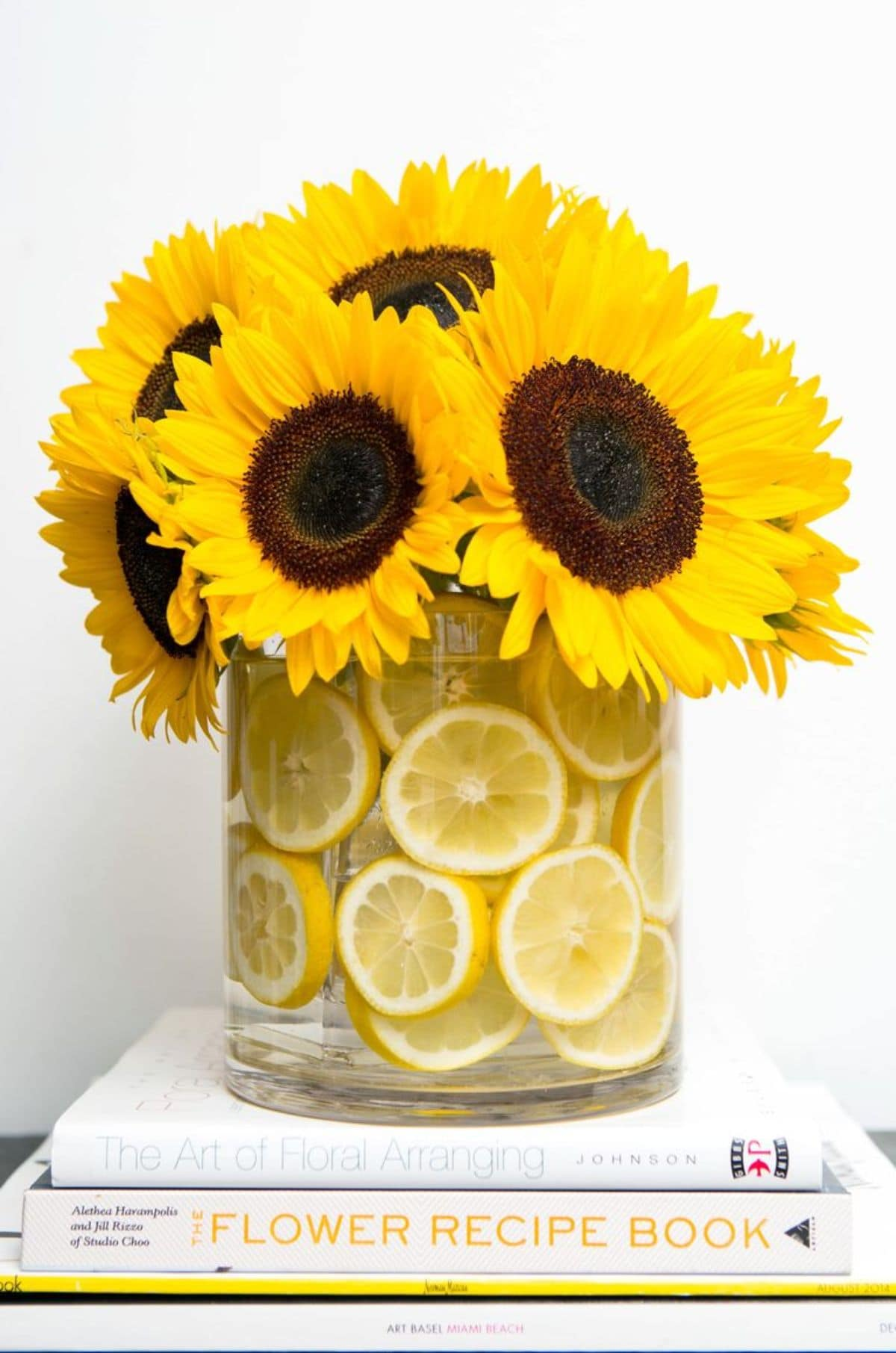 stading ona table is a wide vase filled with lemon slices and sunflowers