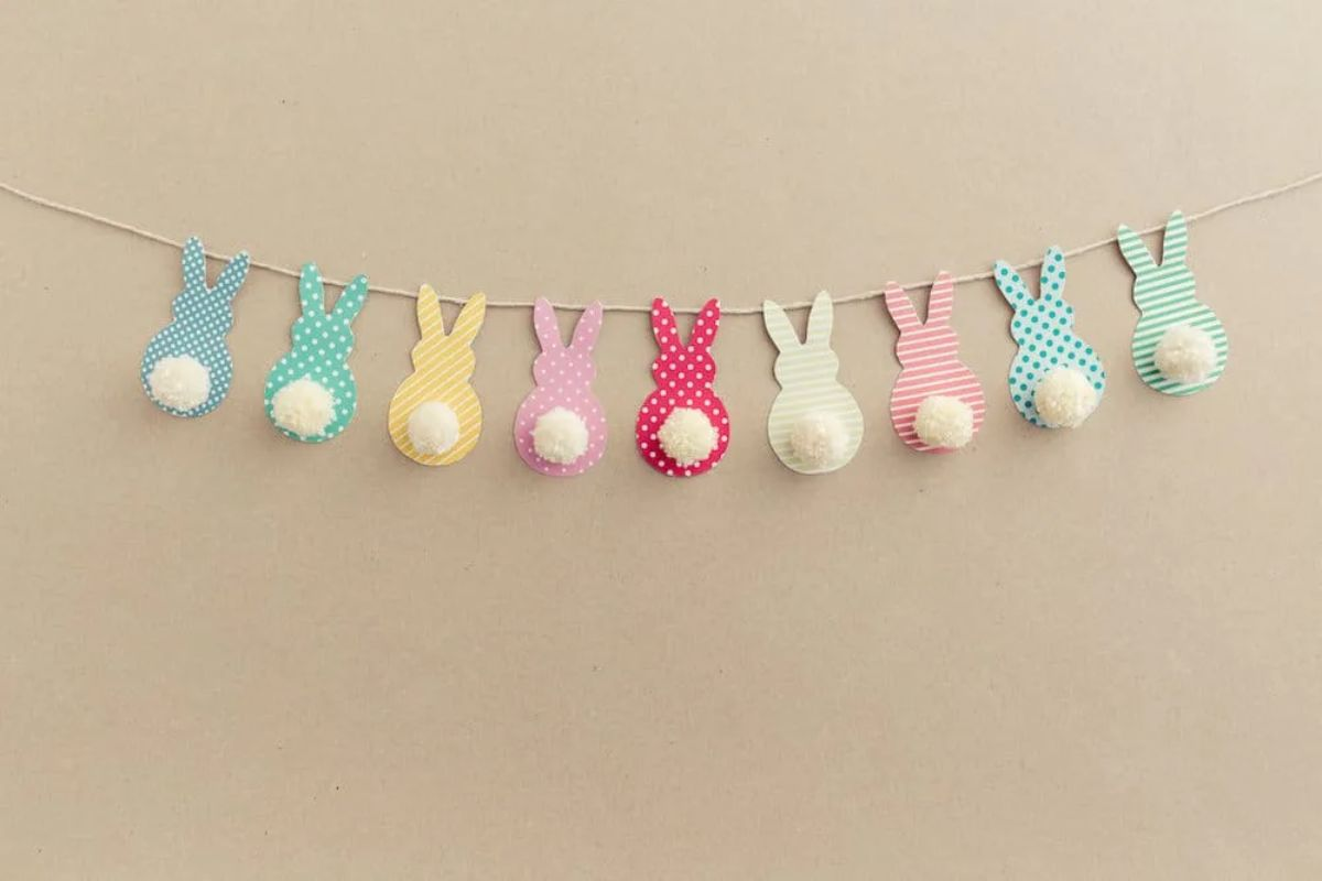 A row of bunnies made of card hanging from a string in blue, yellow, pink, red, white, pink and blue.