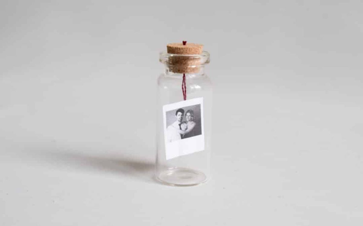 A glass bottle with a cork stopper sits on a surface. Inside is a black and white photograph suspended from the stopper