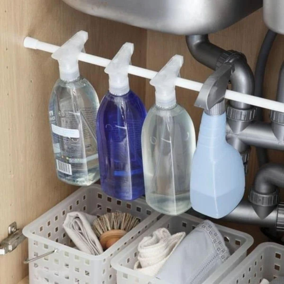 under the kitchen sink a tension rod has been fixed just under a stainless steel bowl. Hanging on teh rod are cleaning product bottles. Underneath are white baskets for other cleaning supplies