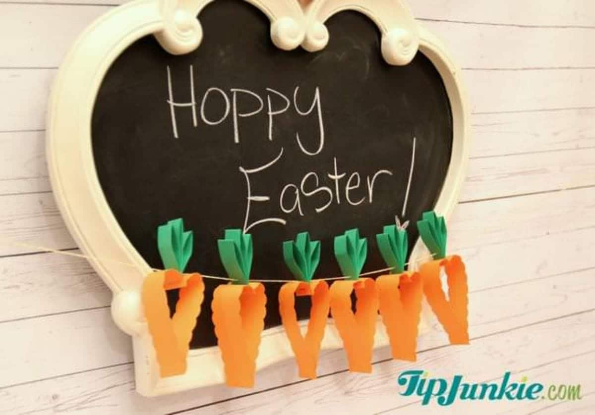 "A blackboard with chalk writing saying ""happy easter!"" sits behind a garland of 3D paper carrots"
