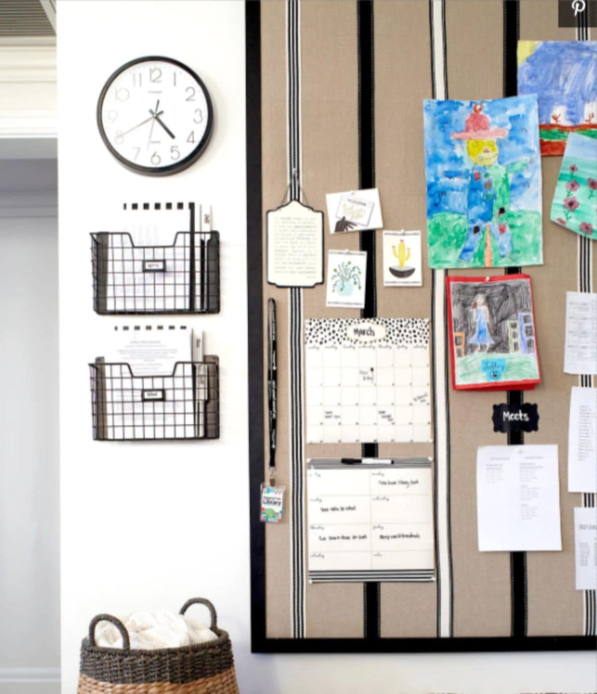 A kitchen wall is shown, with a clock at the top, and two shallow baskets underneat, holding paperwork. On the righ hand side is a display board with artwork and calendars on it.