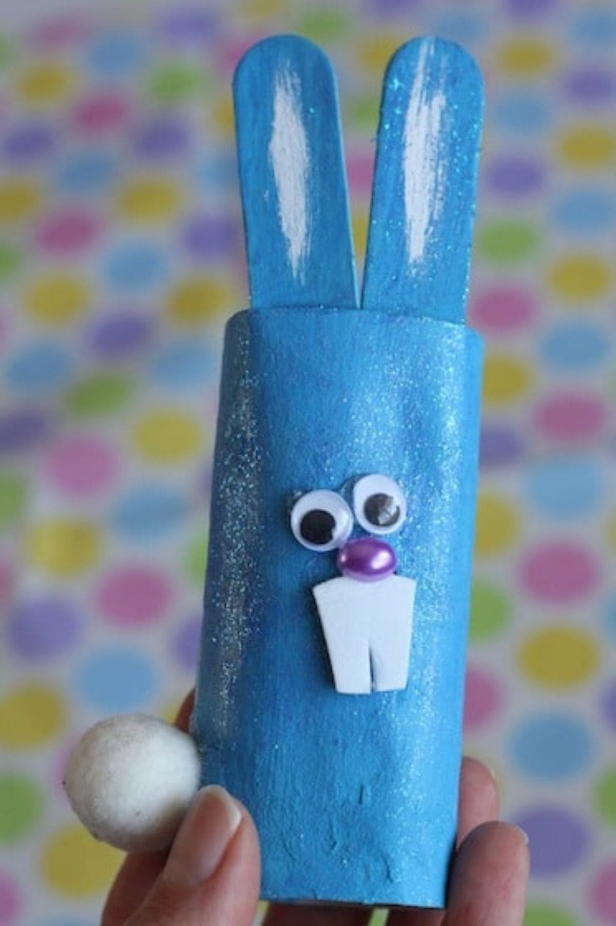 a hand holds a toilet roll painted blue and decorated to look like a rabbit