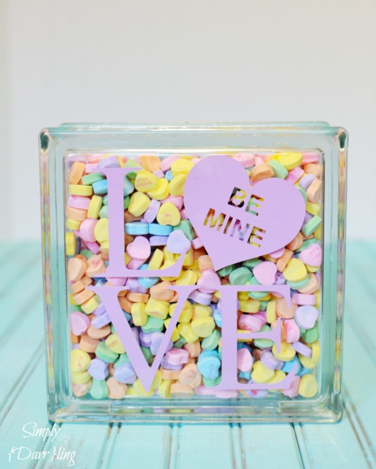 "on a turqoise blurred table is a perspex block with teh words ""LOVE"" on the front in pink. The O is a heart. The block is full of multi-colored candy hearts"
