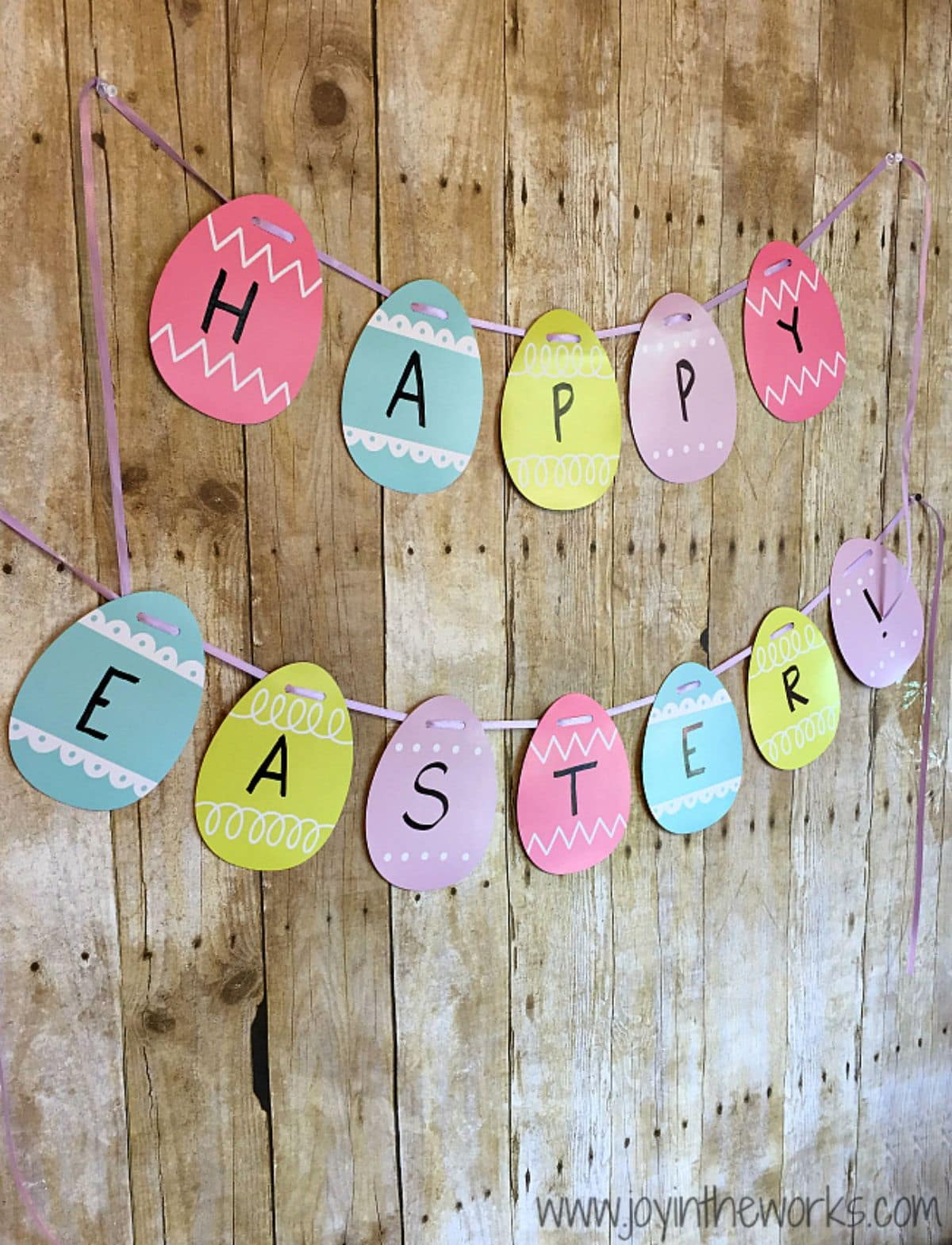 a garland of striped eggs spelling out Happy Easter hang on strings against a wooden backdrop