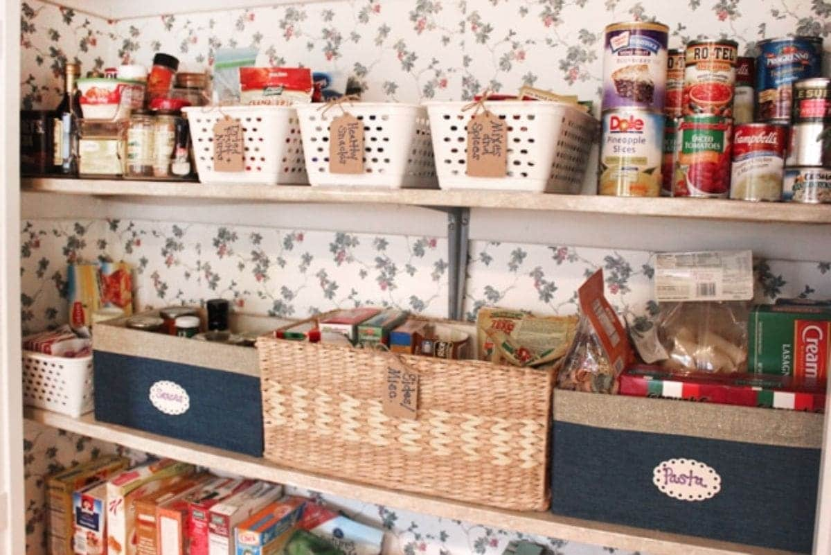 flowery wallpaper with 2 wodden shelves. On each shelf are different baskets with parcel labels attached to them. They are filled with pantry goods