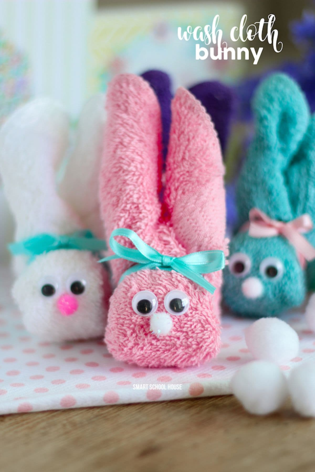 Three bunnies made of differnet colored washcloths sit next to each other