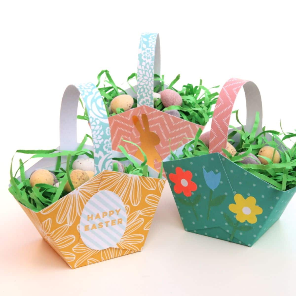 3 paper baskets colored in green, orange and pink and decorated with flowers contain fake grass and chocolate eggs