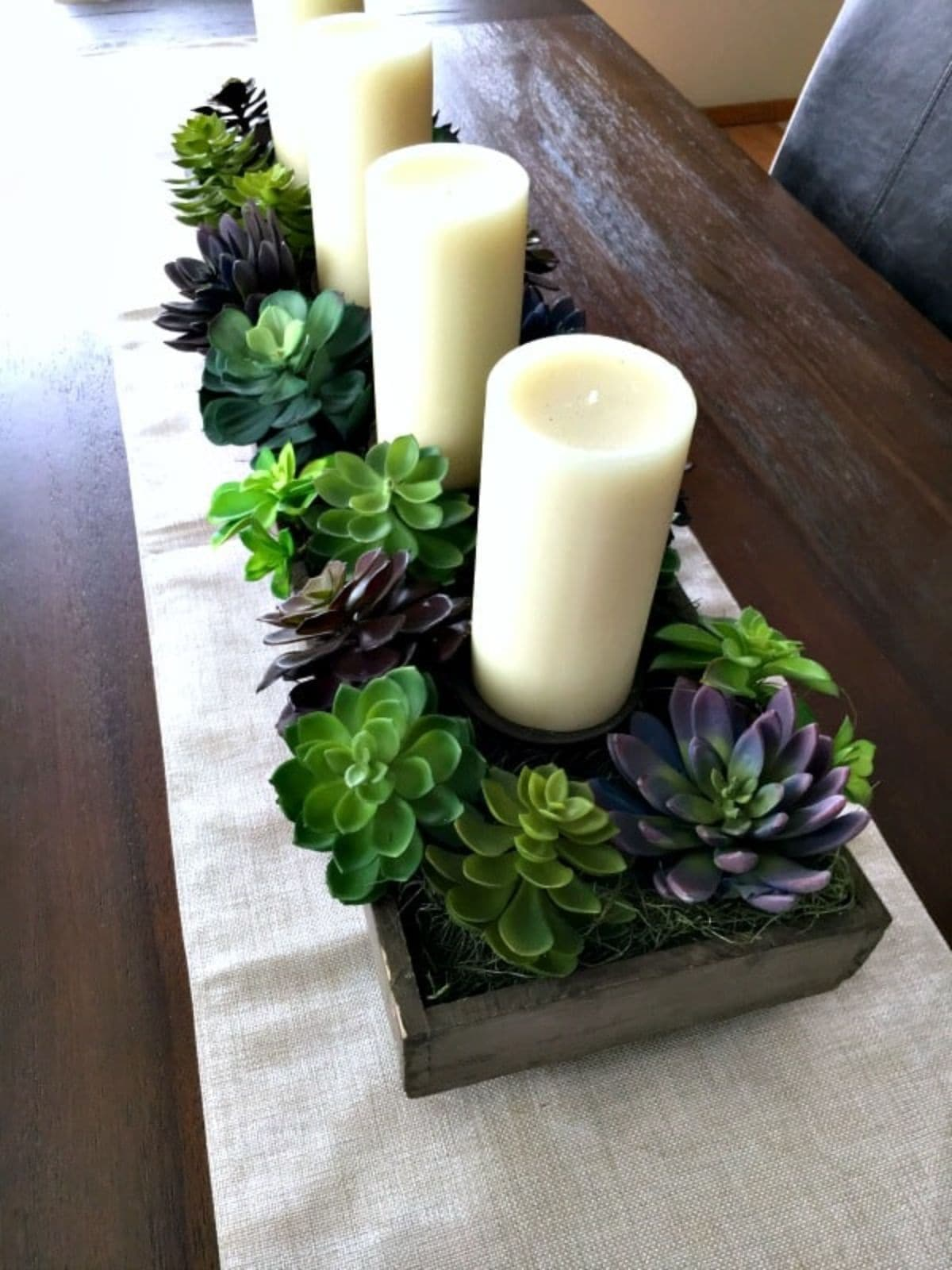 Sitting on a wooden table and a white table runner are 3 church candles surrounded with green wreaths