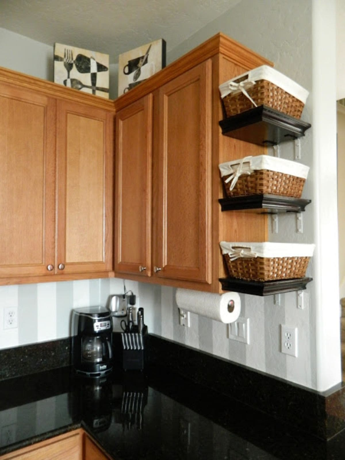THe corner of a kitchen, showing light wood untits. On the edge of the unit 3 shelves have been fixed and wicker baskets sit on each of these shelves.