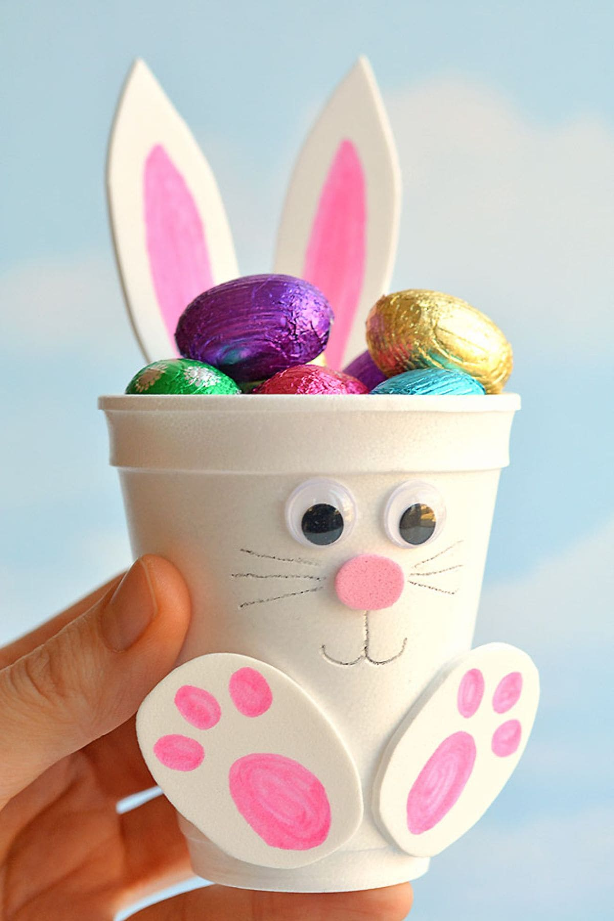 A hand holds a white foam cup decorated to look like a bunny with foil-covered chocolate eggs inside