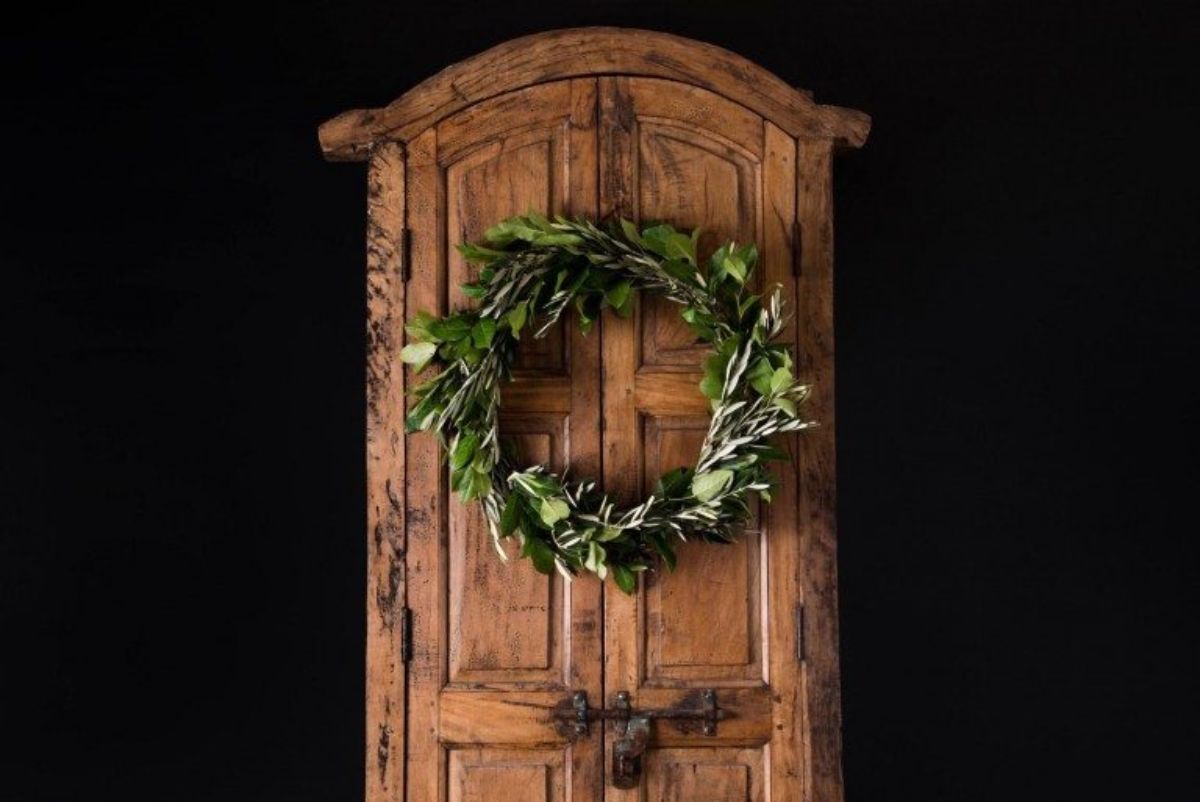 On a wooden carved door hangs a simple green wreath