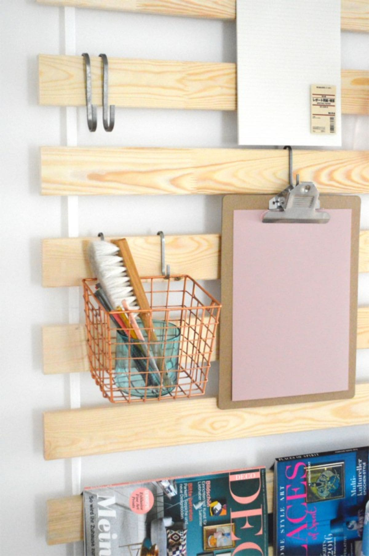 A section of a wooden slatted headboard. Hanging from the slats are hooks. Hanging fro the hooks is a basket with stationery in it and a clipboard