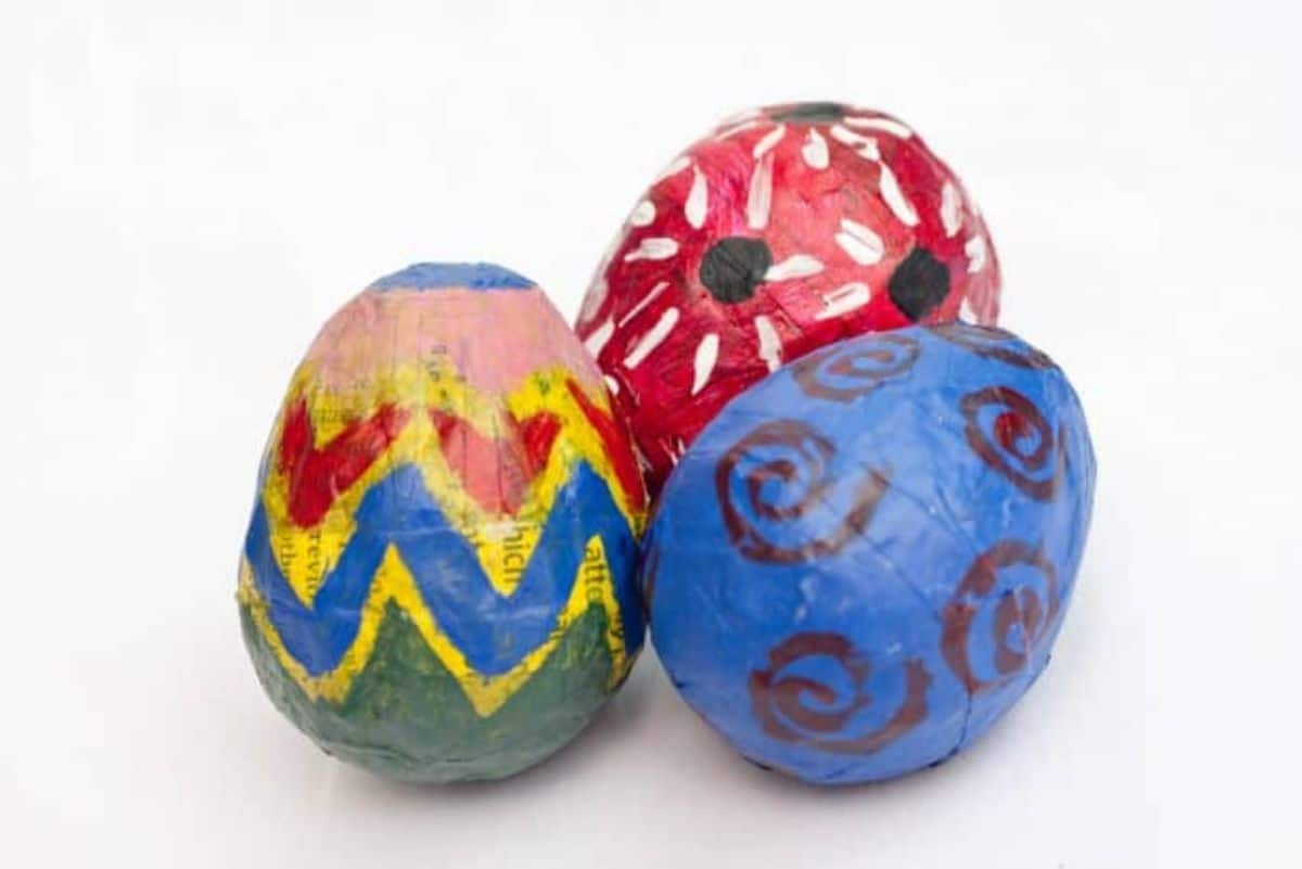 3 eggs sit on a white background. They are decorated in bright colors