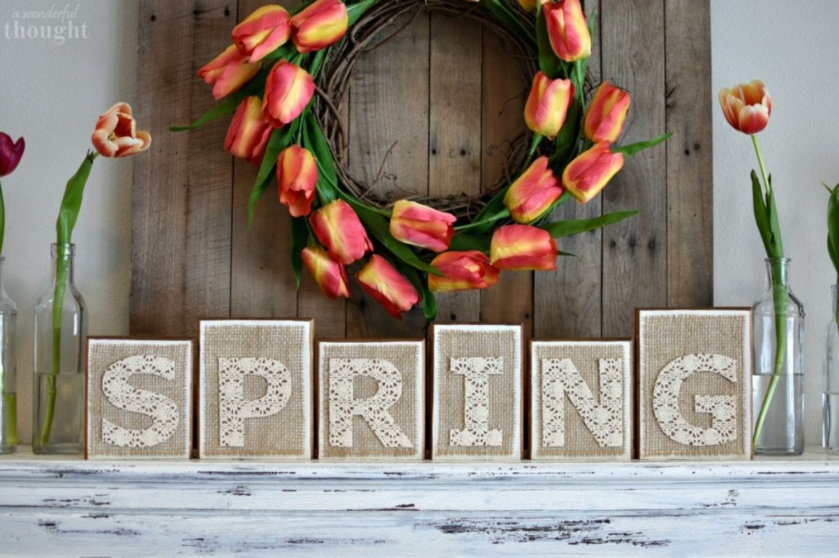 """under a wreath made of orange tuips sit 6 wooden blocks on a mantelpiece spelling out """"Spring"""""""