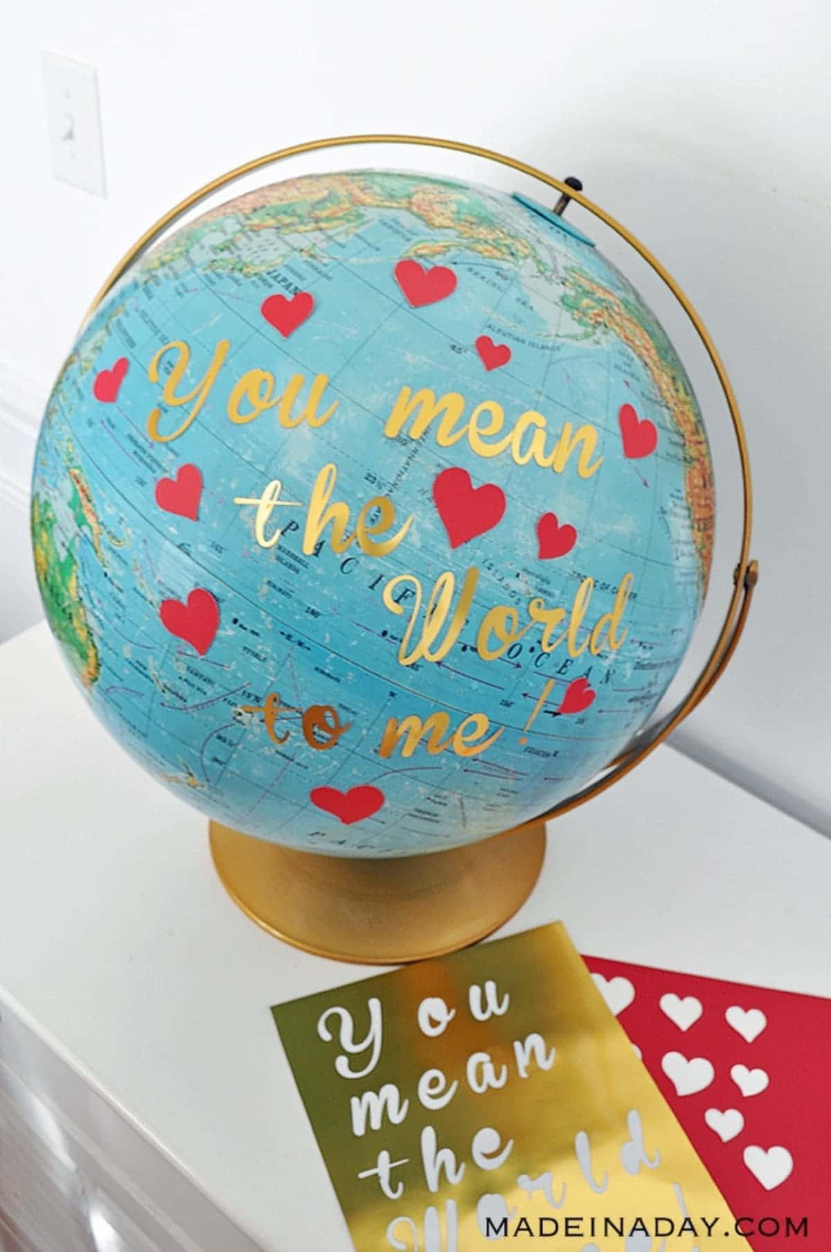 "A globe with a gold stand sits on a white table. The globe is covered in red hearts and the tgold text ""You mean the world to me"""