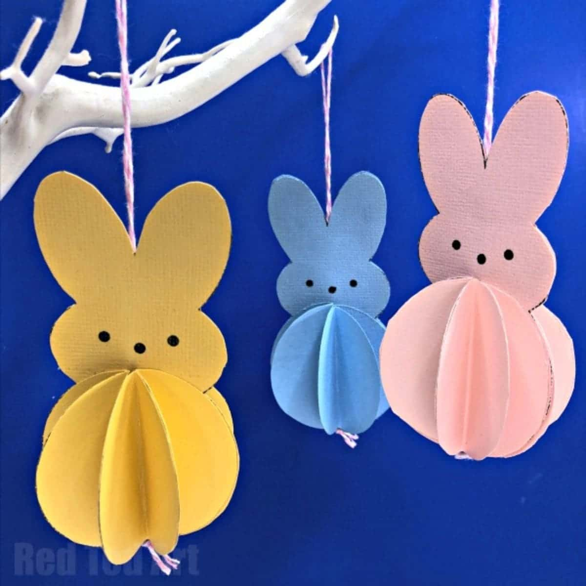 3 paper bunny shapes in orange, blue and pink hang from a white branch against a blue background