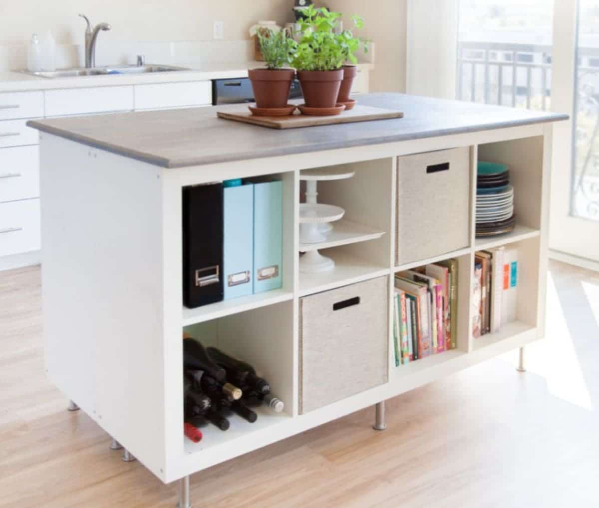 A white IKEA Kallax unit sits on coasters and is filled with wine bottles, folders, plates and baking trays. On top are some potted plants